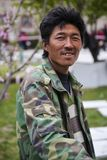 Smiling Tibetan Man Portrait. Pausing from his work, a Tibetan man in a green and olive fatigue jacket over a striped shirt turns to give a smile in a portrait Stock Image