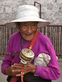 Smiling Tibetan woman with prayer wheel Stock Photo