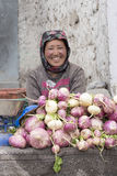 Smiling Tibetan woman sells vegetables at the market in Leh, Ladakh. India Royalty Free Stock Images