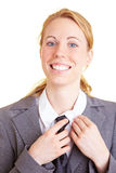 Smiling with a tie. Blond business woman in a suit with a tie stock image