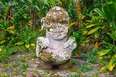 Smiling tiki. Carved stone Polynesian sacred idol statue. Raivavae island, Astral islands, French Polynesia, Oceania. royalty free stock photography