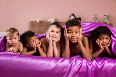 Smiling tired kids on bed. Stock Photo