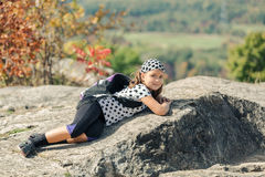 Smiling tired little happy girl lying and relaxing on stone cliffs Royalty Free Stock Image
