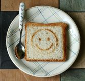 Smiling toast with tea spoon. On the plate Royalty Free Stock Photos