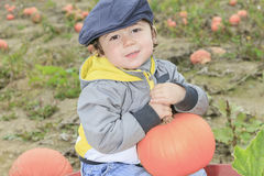 Smiling toddler boy with pumpkin on cold autumn. A Smiling toddler boy with pumpkin on cold autumn day Stock Photos