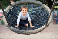 Smiling Toddler Boy on a Swing in the Park Stock Photography