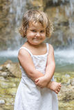 Smiling toddler child girl on waterfall background Royalty Free Stock Photography