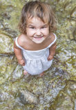 Smiling toddler child girl on waterfall background Royalty Free Stock Image