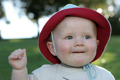 Smiling toddler in floppy hat. Portrait of smiling male toddler in floppy hat outdoors stock image