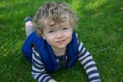 Smiling toddler in garden. Smiling young blond haired toddler in green grass of sunny garden royalty free stock images