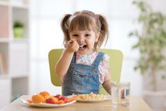 Smiling toddler girl eats at home Stock Image