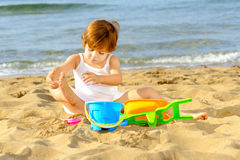 Happy toddler girl playing with her toys on the beach Royalty Free Stock Photography