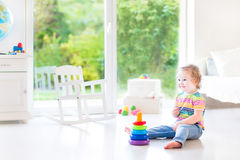 Smiling toddler girl playing with a pyramid toy Royalty Free Stock Images