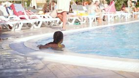 A young girl playing with a ball in an outdoor pool. stock video footage