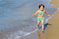 Happy toddler girl running on beach Royalty Free Stock Image