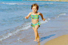Happy toddler girl running on the beach Stock Photography