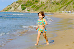 Happy toddler girl running on the beach Stock Images
