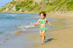 Happy toddler girl running on the beach Royalty Free Stock Image
