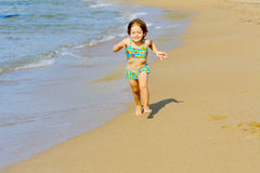Happy toddler girl running on the beach Royalty Free Stock Photography
