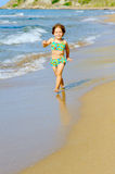 Happy toddler girl running on the beach Stock Image
