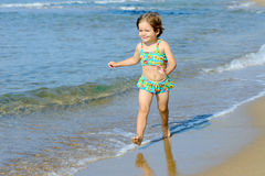 Happy toddler girl running on the beach Royalty Free Stock Photos