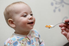Smiling toddler has dinner Royalty Free Stock Photos