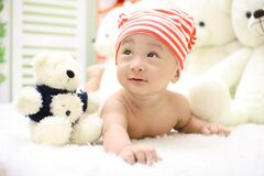 Smiling Toddler Wearing Orange and White Knit Cap Beside Black and White Bear Plush Toy Royalty Free Stock Photos
