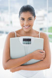 Smiling toned brunette holding scales Stock Photos