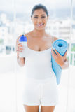 Smiling toned brunette holding sports bottle and exercise mat Royalty Free Stock Images