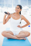 Smiling toned brunette sitting on floor with skipping rope Royalty Free Stock Photos