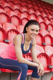 Smiling toned woman sitting on chair in the stadium Stock Images