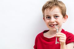 Smiling toothless boy showing a key for fun tooth fairy royalty free stock photography