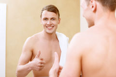 Smiling topless man with thumb-up in front mirror Stock Photo