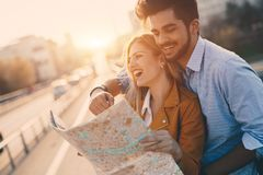 Smiling couple in love traveling with a map outdoors Royalty Free Stock Images