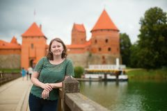 Smiling tourist in front of Trakai castle Royalty Free Stock Images