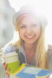 Smiling tourist girl with map and cup of hot beverage Royalty Free Stock Image