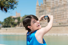 Smiling tourist photographing a landmark Royalty Free Stock Image