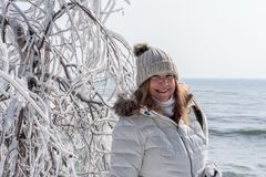 smiling tourist posing next to ice covered tree branches at Cave Point Park, Door County, Wisconsin stock image