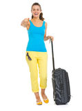 Smiling tourist woman with bag pointing in camera Stock Photo