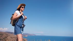 Smiling touristic woman enjoying trekking admiring beautiful nature sea and sky landscape. Low angle. Adorable hiker travel female with backpack contemplative stock footage