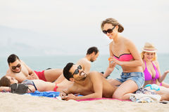 Smiling tourists applying suntan lotion Royalty Free Stock Image