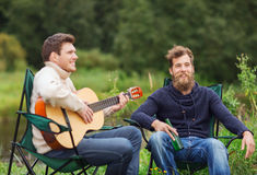 Smiling tourists playing guitar in camping Stock Images