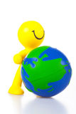 Smiling toy little man rolls forward globe. Stock Photo