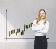 A smiling trader and forex chart with candles. A concept of prosperous portfolio manager. Royalty Free Stock Image