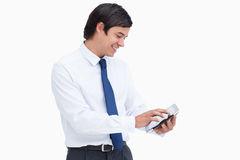 Smiling tradesman using his tablet computer. Side view of smiling tradesman using his tablet computer against a white background Royalty Free Stock Images