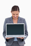 Smiling tradeswoman looking down at her laptop Royalty Free Stock Photography