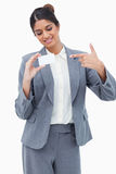 Smiling tradeswoman pointing at blank business card Royalty Free Stock Images