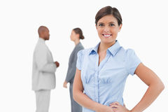Smiling tradeswoman with talking associates behind her Royalty Free Stock Photos