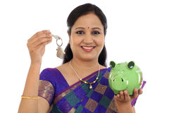 Smiling traditional woman holding piggy bank and house key Stock Photography