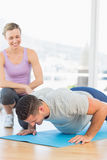 Smiling trainer assisting man with push ups. Smiling female trainer assisting men with push ups at gym Stock Photo